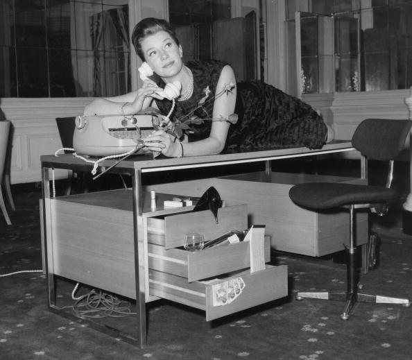 Actress Lois Maxwell who plays Miss Moneypenny in the Bond films drapes herself across a desk designed by Intra Design Ltd a company set up by the Rank Organisation. The desk was part of a display at the Savoy Hotel of the company's designs. (Photo by B Marshall/Getty Images)