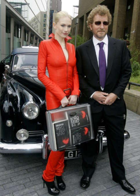 Model Tuuli Shipster holds a briefcase with copies of the new James Bond novel with author Sebastian Faulks at the book's launch in London, Tuesday, May 27, 2008. The new James Bond novel is being published for the centenary of bond creator Ian Fleming's birth. (AP Photo/Kirsty Wigglesworth)