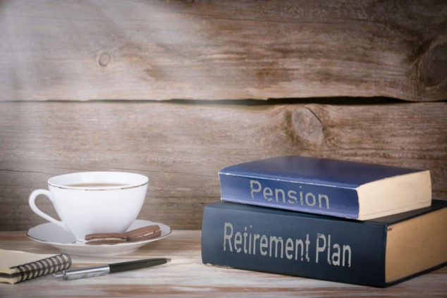 Retirement Plan and Pension. Stack of books on wooden desk.