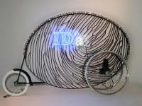 Ida, 7' x 2' x 5', fabricated mild steel, bicycle parts, plasma cut steel letters, gold leaf, argon tube, electronics