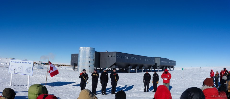 The South Pole Fire Crew holds their axes while Station Manager Bill Coughran reads a poem in memory. The canadian flag flies next to the geographic pole.