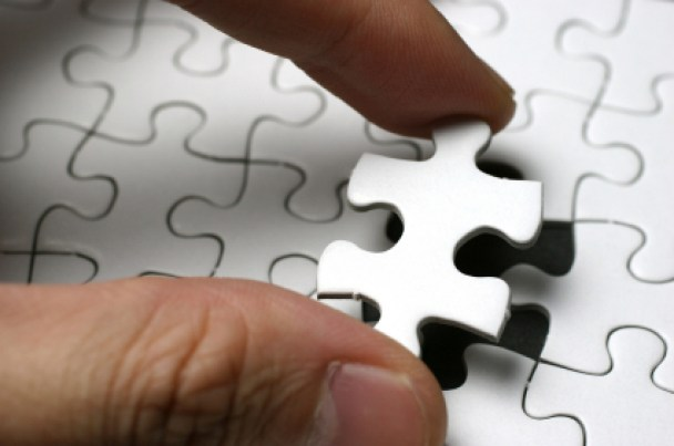 man fitting puzzle in piece