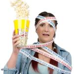 teenage girl wrapped by admissions tickets holding popcorn in sh