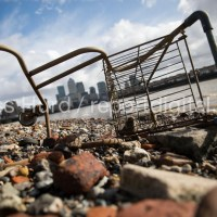 Abandoned washed up Tesco shopping trolley with a view of Canary Wharf, River Thames, Limehouse, London Docklands.