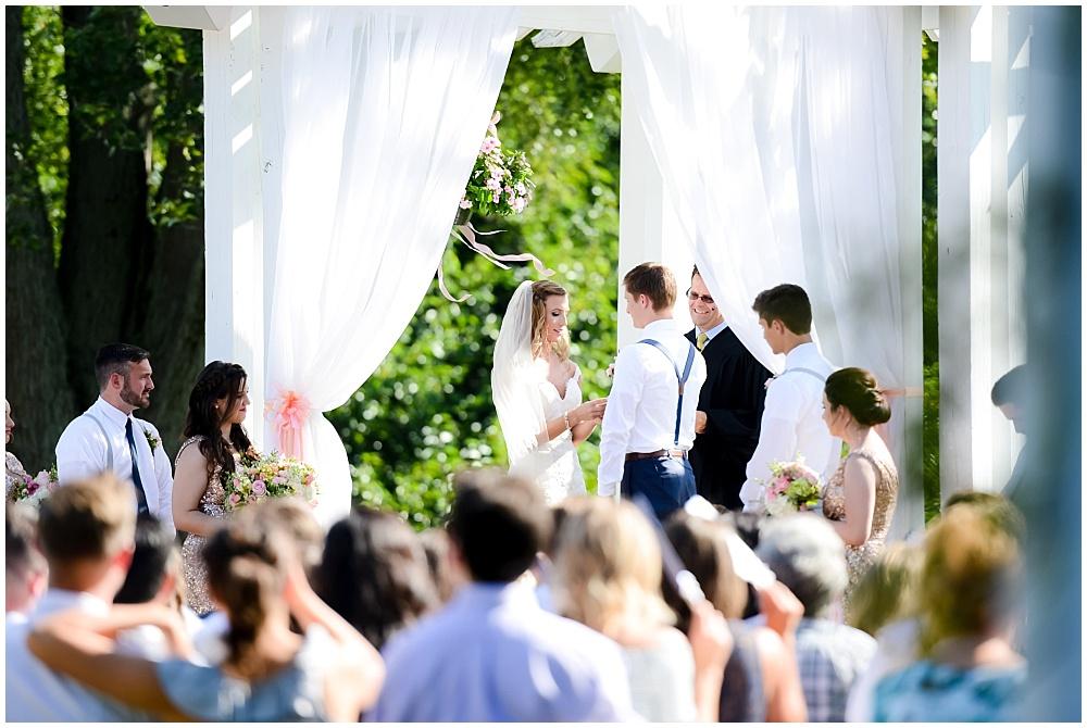 Wedding ceremony with white fabric draping under a gazebo | Mustard Seed Gardens Wedding by Sara Ackermann Photography & Jessica Dum Wedding Coordination