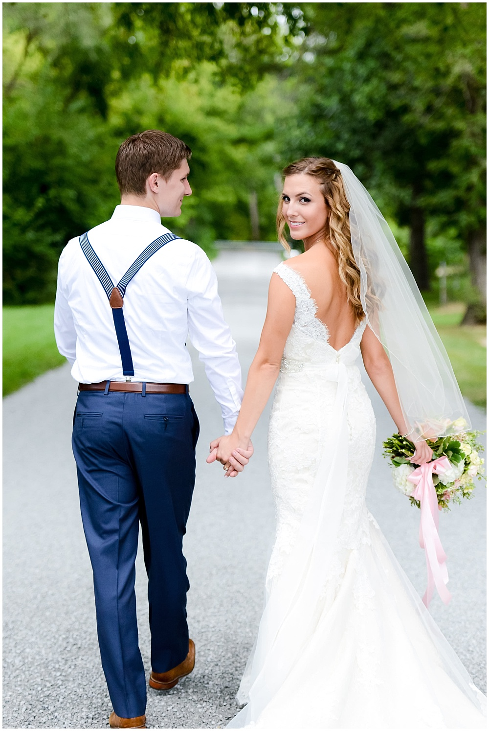 Back of lace wedding dress with groom's navy suspenders | Mustard Seed Gardens Wedding by Sara Ackermann Photography & Jessica Dum Wedding Coordination