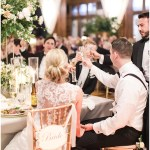 bride and groom toasting; ivory and gold chair signs; lace back wedding dress; Scottish Rite Cathedral Indianapolis Wedding; neutral floral and greenery wedding| Ivan & Louise Images and Jessica Dum Wedding Coordination
