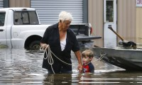 Richard Rossi and his 4 year old great grandson Justice wade through water in search of higher ground after their home took in water in St. Amant, Louisiana, U.S., August 15, 2016.  REUTERS/Jonathan Bachman   (Newscom TagID: rtrleight131241.jpg) [Photo via Newscom]