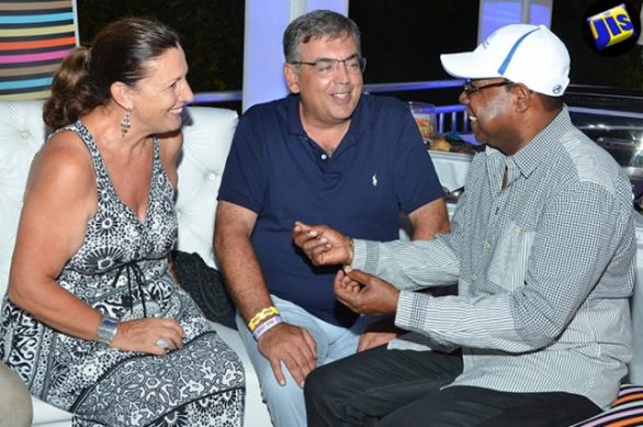 Tourism Minister, Hon. Edmund Bartlett (right), is in light conversation with the General Manager of Half Moon Hotel in Rose Hall, Sandro Fabris and his wife, Doris, in the Jamaica Tourism Board (JTB) booth. The occasion was Saturday night's (July 23) staging of Reggae Sumfest 2016 at the Catherine Hall Entertainment Centre in Montego Bay.