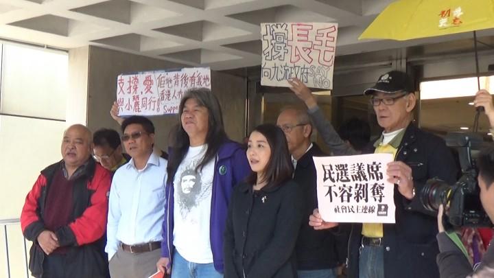梁國雄和劉小麗在支持者陪同下抵達法院應訊。(影片截圖)