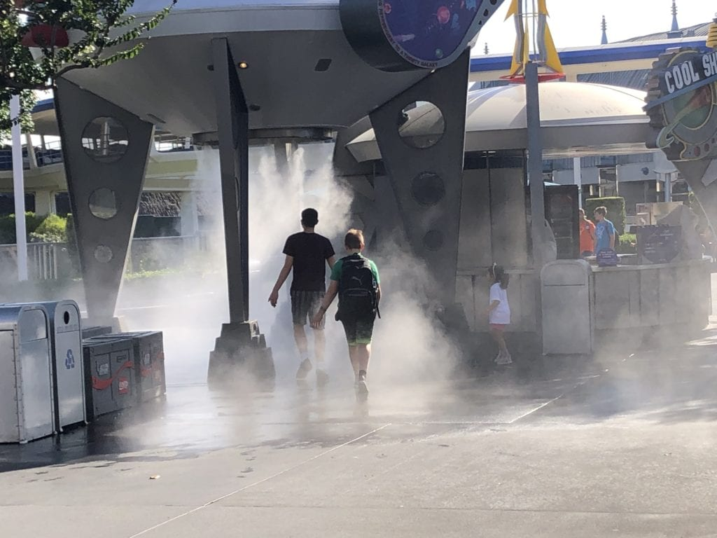 The boys walking into a misting station at Magic Kingdom, Disney World, Orlando, FLorida
