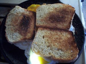 Quick before the egg white set up, slap the toast down on each egg and Spam slice, untoasted side down.