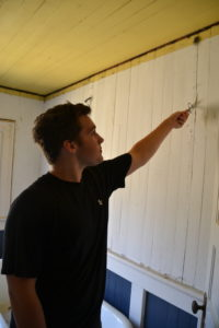 Daniel removes staples and nails left after quilting wall covering is removed in bathroom.