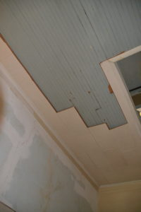 Beadboard peaks out beneath ceiling tile.