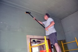 On scaffolding, Scott cleans walls to prepare for repair of plaster in our living room.