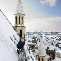 Snow being swept from the rooftops of the York Minster