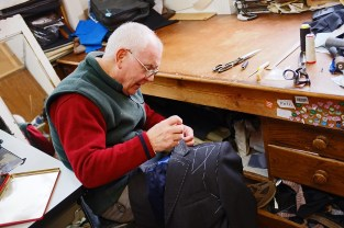 Mel Woodhead removing stitches in the construction of a suit jacket.