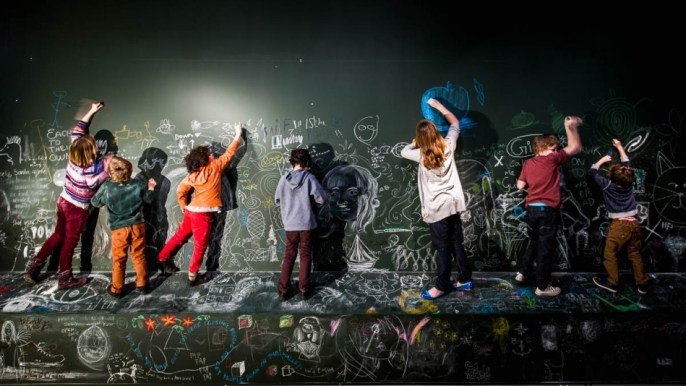 A line of children reach up the draw on the walls at York Art Gallery.