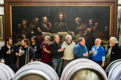 Rev Matt Woodcock with real ale drinkers in front of a painting of Jesus and the Last Supper