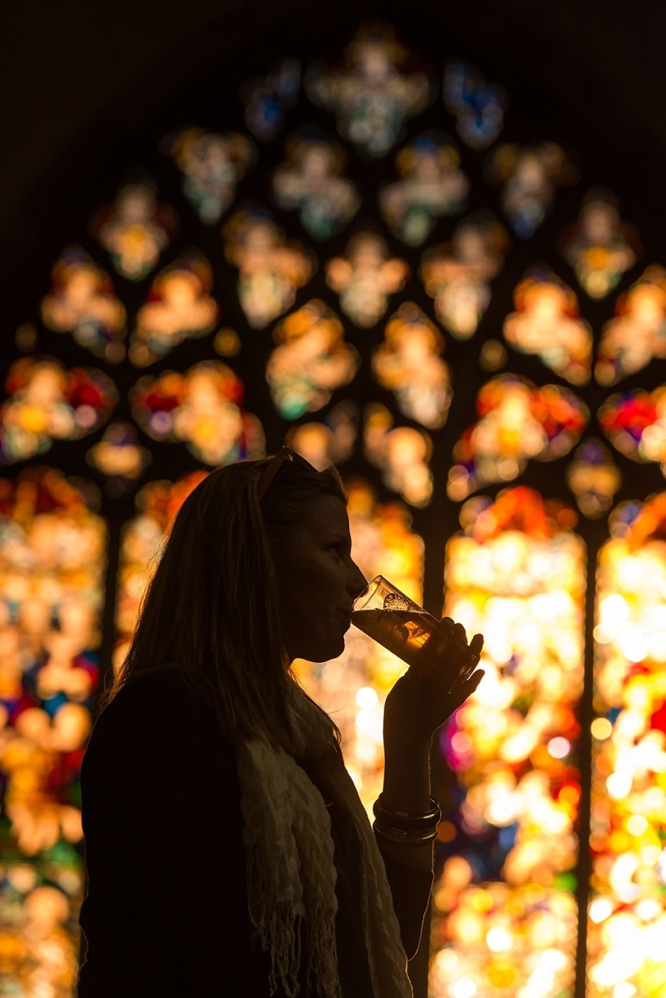A girl drinks a glass of ale in front of a large stained glass window
