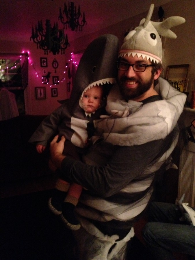 Man dressed as Sharknado holding a small child dressed as a shark.