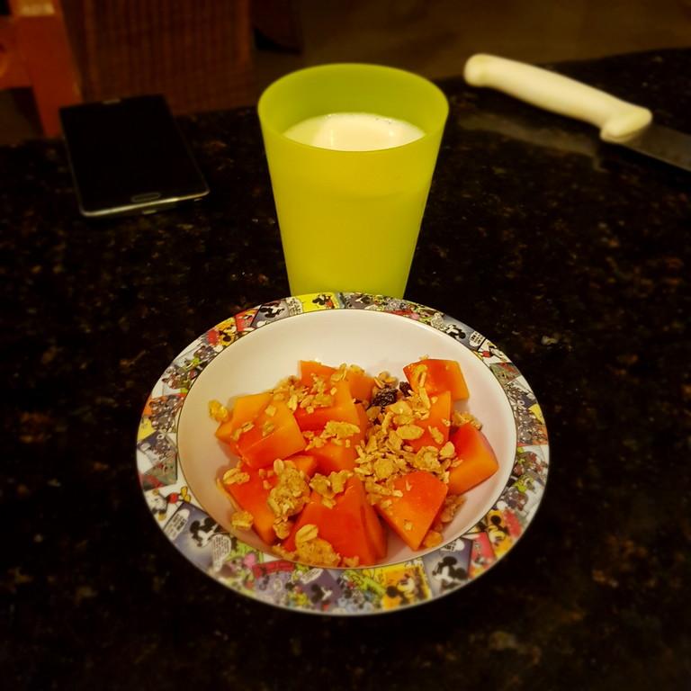 Una taza de papaya con granola y leche
