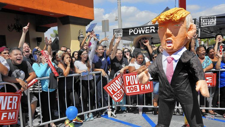 """Onlookers yell at a Donald Trump piñata during a """"Take It Out on Trump"""" event in East Los Angeles in September 2015. (Credit: Mel Melcon/Los Angeles Times)"""