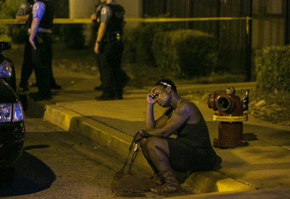 A woman sits on the curb as Chicago police investigate an August scene where gunfire at a birthday party left a man dead and a woman injured. (Credit: Ashlee Rezin/Chicago Sun-Times)
