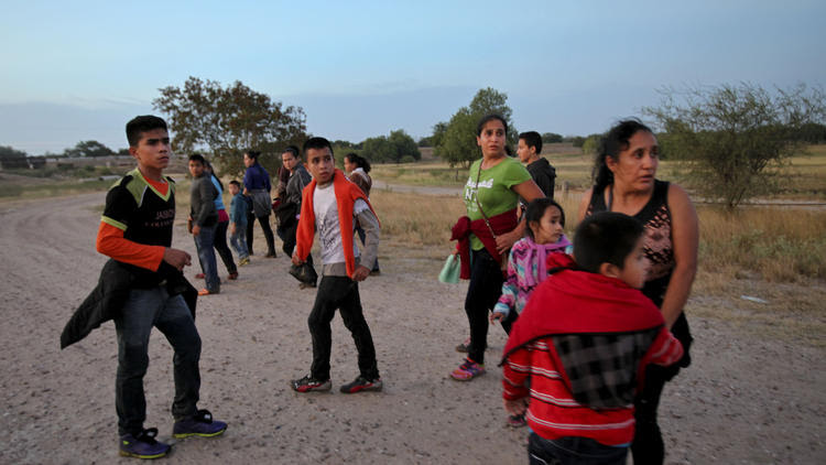 Migrants from Guatemala turn to face a local law enforcement official, not shown, giving them instructions after they crossed the Rio Grande near McAllen, Texas, in 2014. (Credit: Michael Robinson Chavez/Los Angeles Times)