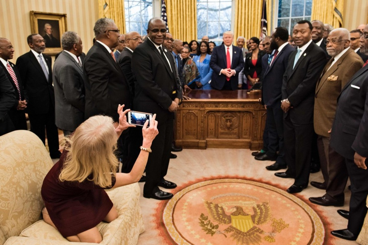 Counselor to the President Kellyanne Conway takes a photo Tuesday in the Oval Office. (Credit: Pool photo by Brendan Smialowski/Agence France-Presse)
