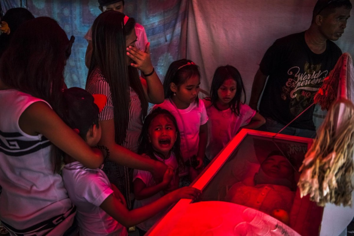 "In this photo by Daniel Berehulak taken in the Philippines, Jimji, 6, cries ""Papa!"" in anguish as she and other relatives await the start of the funeral for her father, Jimboy Bolasa, 25. His body, showing signs of torture along with gunshot wounds, was found under a bridge."