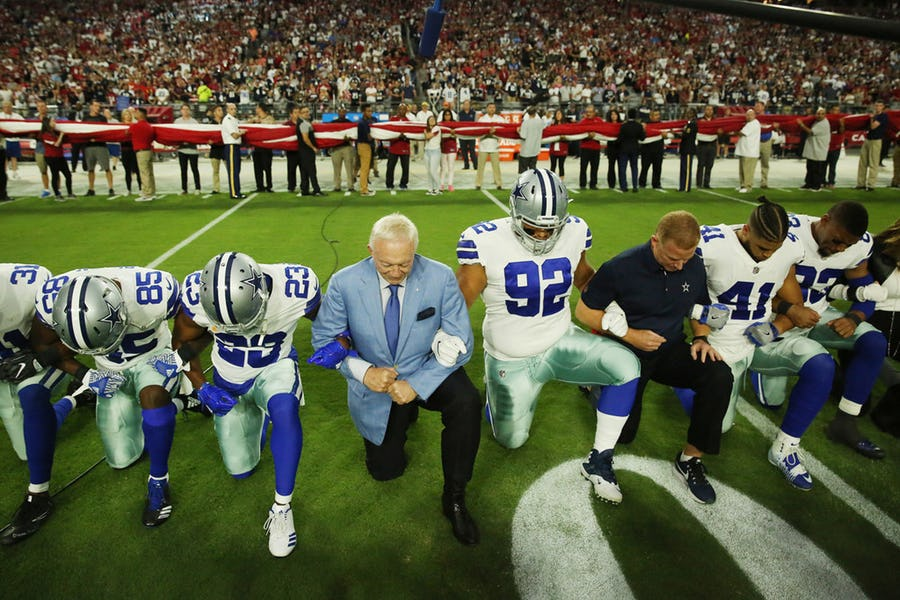 Dallas Cowboys players and staff, including owner Jerry Jones and head coach Jason Garrett, all take a knee before the singing of the National Anthem prior to the start of a game against the Arizona Cardinals at University of Phoenix Stadium on Monday (Credit: Andy Jacobsohn/Dallas Morning News)