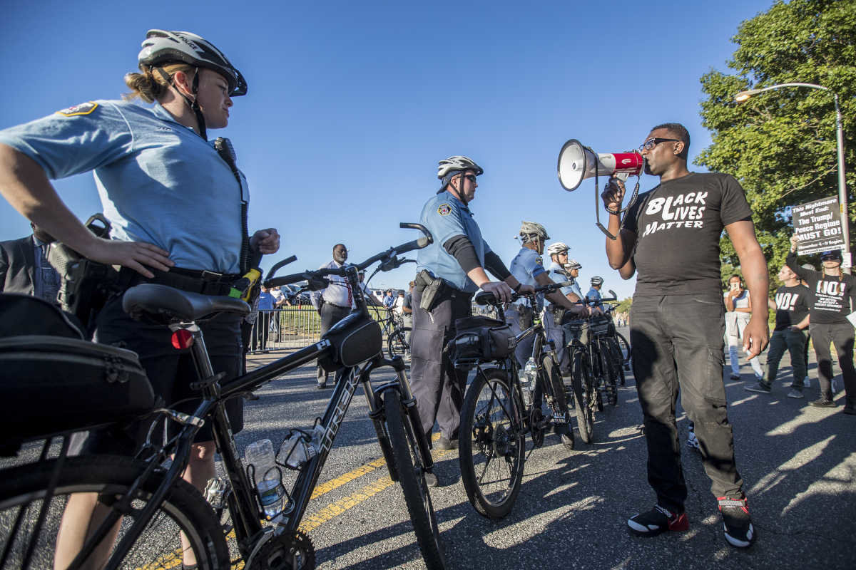 Asa Khalif, right, a national organizer for Black Lives Matter, uses his bullhorn to address the line of Philadelphia Bicycle Police Officers blocking the entrance to the Fraternal Order of Police headquarters on Sunday. (Credit: Michael Bryant/Philadelphia Inquirer)