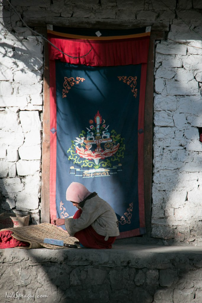 A novice monk squats in the sun at the Muktinath Monastery, Lower Mustang. A boy can take novice vows at age 7, when he is big enough to scare a crow away. Full ordination can be bestowed at age 20, the intervening years filled with study and learning of the five great books of Buddhism.