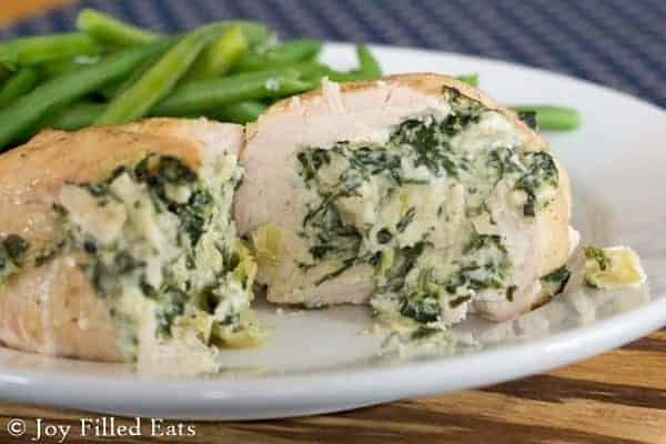 Spinach & Artichoke Stuffed Chicken Breasts are fancy enough for company but easy enough for every day. They freeze well, are low carb, gluten free & THM S.