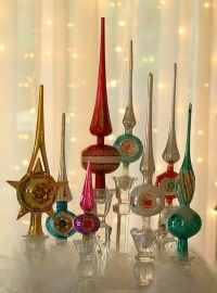 Vintage tree toppers displayed in glass candle holders ...