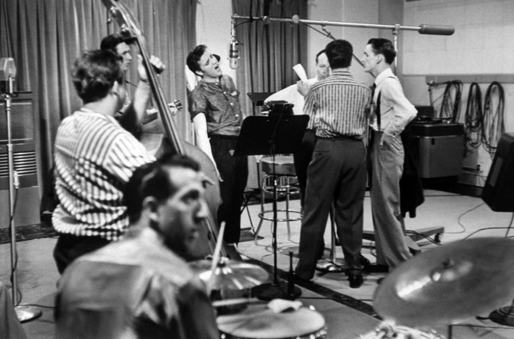 Elvis Presley recording a new song in an unident. recording studio, backed up by the Jordanaires vocally (made up of Gordon Stoker, Neal Matthews, Jr., Hoyt Hawkins and Hugh Jarrett), Bill Black on bass and D.J. Fontana on drums. (Photo by Don Cravens/The LIFE Images Collection/Getty Images)