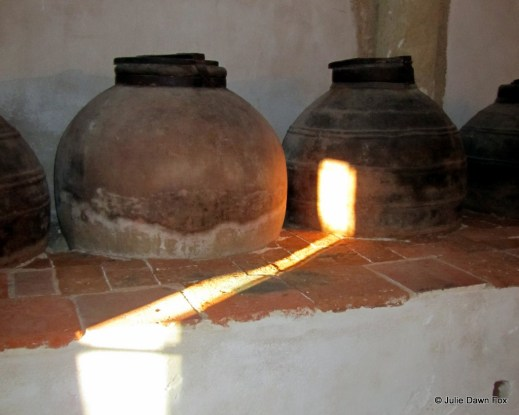 shaft of sunlight on ceramic olive oil pot