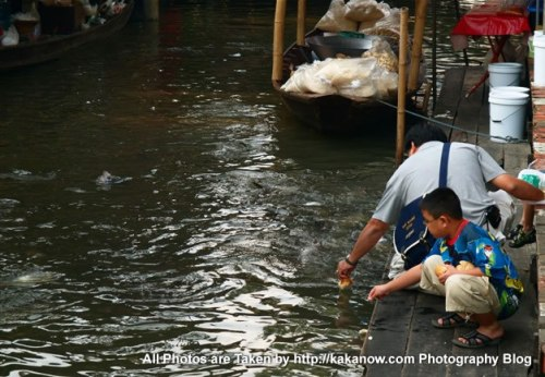 Thailand travel, Bangkok, Floating Market, a father and his son feed the fish. Photo by KaKa.