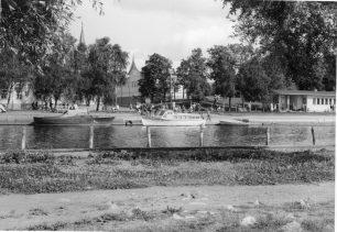 Näkymä Sorvakon rannasta kohti Rantakatua ja kaupungin keskustaa. Keskellä laiturissa oleva vesibussi edustaa tyyliltään 1950-luvun puurunkoista vesibussimallia. Vesibussit veivät tuohon aikaan ihmisiä muun muassa kaupungin omistamaan Koiviston lomasaareen. Vesibussin takana Uudenkaupungin yhteislyseon rakennus, joka toimii nykyisin kaupunginkirjastona. Oikealla Kalarannan seisakkeen pieni valkoinen rakennus. Kuvaaja Olavi Ruusuvuori.