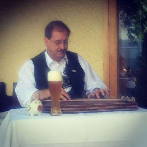 This picture of a traditionally-dressed man serenading hotel guests was taken at breakfast, at 0900. Notice the beer?