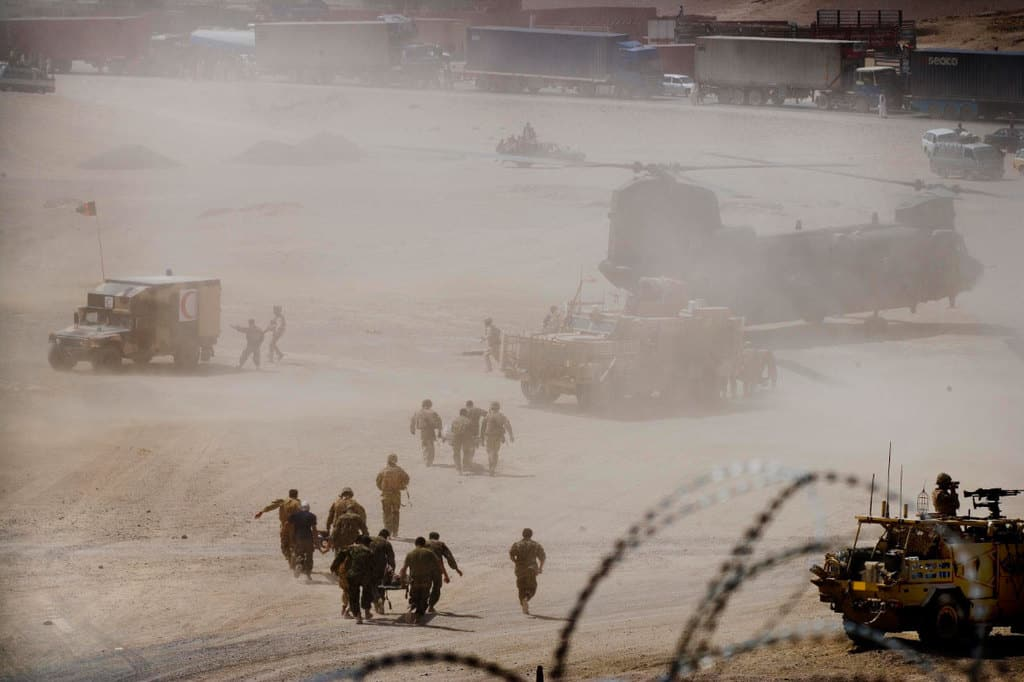 Soldiers from 1 Scots Guards and the Afghan National Army (ANA) run with stretchers bearing civilian casualties. Kate Holt.