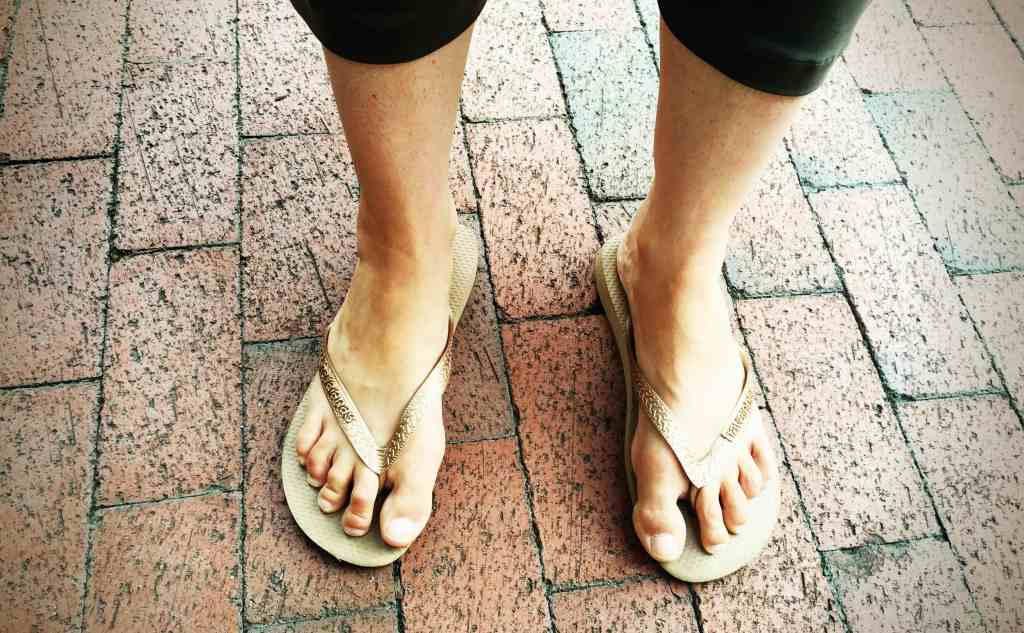 A photograph of the author's feet in gold flip-flops.