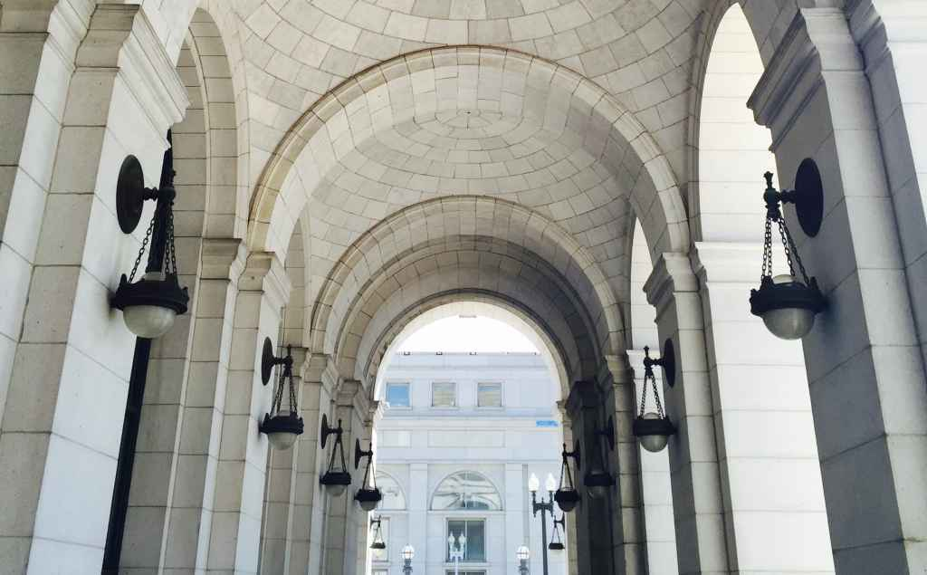 Alt Text: A photograph of the Union Station breezeway, showing arches made of white stone and dark metal sconces on the side-columns. At the end of the breezeway another building is just visible.