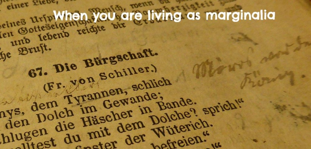 """Alt Text: A photograph of poetry in German with handwritten text in the margin. Typed on top of the photograph is this phrase: """"When you are living as marginalia."""""""