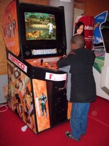 Petit garçon jouant à Soul Calibur 1 sur borne d'arcade