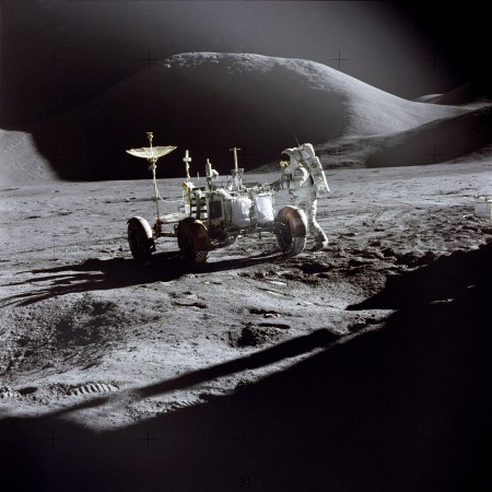 """Lunar module pilot James Irwin works at the Lunar Roving Vehicle during the first Apollo 15 lunar surface extravehicular activity at the Hadley-Apennine landing site. The shadow of the Lunar Module """"Falcon"""" is in the foreground. This view is looking northeast, with Mount Hadley in the background. This photograph was taken by mission commander David Scott. (Photo: NASA)"""