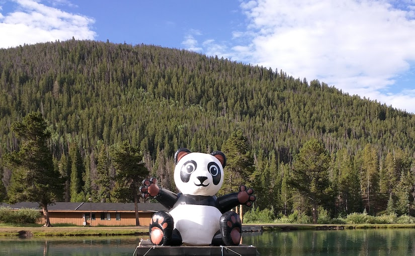 inflatable panda on a pond in Colorado under a blue, cloudy sky.