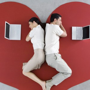 Man and woman lying back to back on large heart, both looking at laptop computers