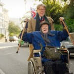 The Lady In The Van - Dame Maggie Smith as Miss Shepherd being pushed in a wheelchair by Alex Jennings as Alan Bennett in